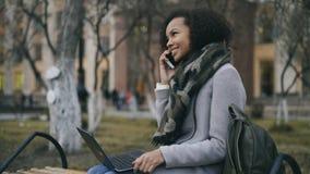Aantrekkelijk Afrikaans Amerikaans studentenmeisje die haar telefoonzitting op bank met laptop computer in openlucht spreken Stock Fotografie