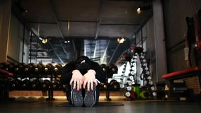 Aantrekkelijk atletisch donkerbruin meisje die het uitrekken doen zich terwijl het zitten op een sportenmat in de gymnastiek stock videobeelden