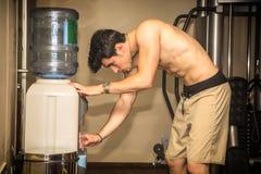 Aantrekkelijk atletisch jonge mensen drinkwater binnen royalty-vrije stock afbeelding