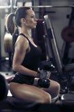 Aantrekkelijk atletisch meisje die bicepsen op een donkere achtergrond maken Stock Afbeeldingen