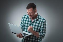 Aantrekkelijk bedrijfsmensenmodel in groen overhemd bij het grijze werken met laptop, die iets tonen door linkerhand Stock Afbeelding