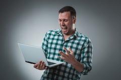 Aantrekkelijk bedrijfsmensenmodel in groen overhemd bij het grijze werken met laptop, die iets tonen door linkerhand Royalty-vrije Stock Fotografie