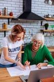 Aantrekkelijk bejaarde die jong-volwassenendame om het helpen met documenten vragen stock foto