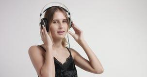 Aantrekkelijk blond meisje in loungewear en hoofdtelefoons stock footage