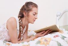 Aantrekkelijk blond meisje met hairdress het lezen Stock Foto's