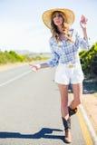 Aantrekkelijk blonde die bij de kant van de weg liften Royalty-vrije Stock Foto's