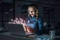 Aantrekkelijk blonde die glazen in donker bureau dragen die laptop met behulp van M royalty-vrije stock foto