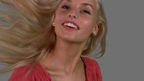 Aantrekkelijk blonde die haar haar omhoog op grijze achtergrond schudden dicht omhoog stock videobeelden