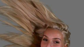Aantrekkelijk blonde die haar haar omhoog op grijze achtergrond werpen dicht omhoog stock videobeelden