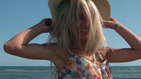 Aantrekkelijk blonde die met strohoed op strand draaien stock videobeelden