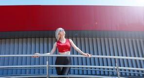 Aantrekkelijk blonde in rode bovenkant en zwarte beenkappen die in een modieus patroon stellen Dag, openlucht Royalty-vrije Stock Fotografie