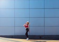 Aantrekkelijk blonde in rode bovenkant en zwarte beenkappen die in een modieus patroon stellen Dag openlucht Concept het sportlev Stock Foto