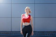 Aantrekkelijk blonde in rode bovenkant en zwarte beenkappen die tegen modieus patroon stellen Dag openlucht Royalty-vrije Stock Foto's