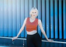 Aantrekkelijk blonde in rode bovenkant en zwarte beenkappen die tegen s stellen Stock Afbeeldingen