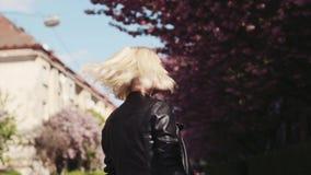 Aantrekkelijk blondemeisje die in leerjasje van de kersenbloesem in de stad, draaien aan camera en glimlachen charmingly genieten stock footage