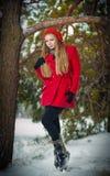 Aantrekkelijk blondemeisje met handschoenen, rode laag en de rode sneeuw van de hoeden stellende winter. Schoonheidsvrouw in het d Royalty-vrije Stock Afbeeldingen