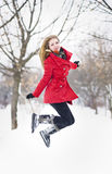 Aantrekkelijk blondemeisje met handschoenen, rode laag en het rode hoed stellen in de wintersneeuw. Mooie vrouw in het de winterla Stock Fotografie