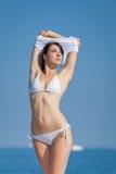 Aantrekkelijk brunette in het witte swimwear ontkleden op het strand Stock Foto's
