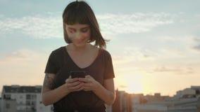 Aantrekkelijk brunette met gadget op dak bij zonsondergang stock footage