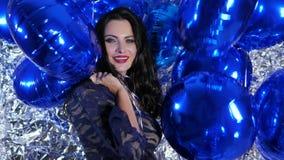 Aantrekkelijk brunette met gekleurde ballons op glanzende muur als achtergrond stock footage