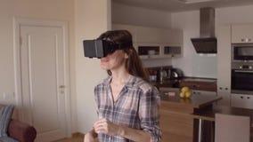 Aantrekkelijk donkerbruin meisje die haar telefoonvr hoofdtelefoon thuis met behulp van Virtuele werkelijkheidsglazen in actie 4K stock videobeelden