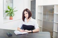 Aantrekkelijk donkerharige die een zwart-witte blousezitting dragen bij het bureau in het bureau Stock Foto's