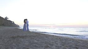 Aantrekkelijk enloved het jonge paar kussen op het strand bij avond Romantisch wittebroodswekenconcept stock footage
