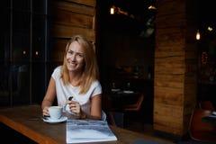 Aantrekkelijk gelukkig hipstermeisje met goede stemming die terwijl het zitten alleen in het moderne binnenland van de koffiewink Royalty-vrije Stock Foto