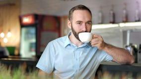 Aantrekkelijk gelukkig mannetje goede tijd het drinken koffie hebben of thee die camera bekijken stock video
