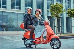 Aantrekkelijk gelukkig paar, een knappe mens en een sexy wijfje die samen op een rode retro autoped in een stad berijden stock foto's