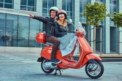 Aantrekkelijk gelukkig paar, een knappe mens en een sexy wijfje die samen op een rode retro autoped in een stad berijden stock foto
