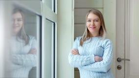 Aantrekkelijk glimlachend Europees meisje dichtbij venster met gekruist handen middelgroot schot stock video