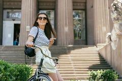 aantrekkelijk glimlachend meisje die smartphone gebruiken terwijl het zitten op fiets dichtbij de mooie bouw met kolommen royalty-vrije stock foto