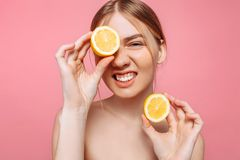 Aantrekkelijk glimlachend meisje met schone huid en citroen op een roze achtergrond stock afbeelding