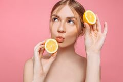 Aantrekkelijk glimlachend meisje met schone huid en citroen op een roze achtergrond stock afbeeldingen