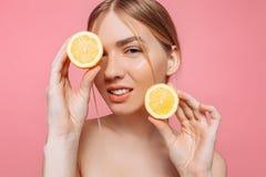 Aantrekkelijk glimlachend meisje met schone huid en citroen op een roze achtergrond stock foto's