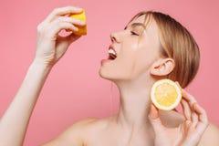 Aantrekkelijk glimlachend meisje met schone huid en citroen op een roze achtergrond royalty-vrije stock afbeeldingen