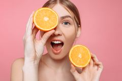 Aantrekkelijk glimlachend meisje met schone huid en oranje stukken op een roze achtergrond royalty-vrije stock fotografie