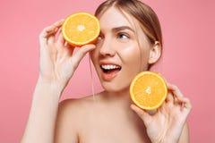 Aantrekkelijk glimlachend meisje met schone huid en oranje stukken op een roze achtergrond royalty-vrije stock afbeelding