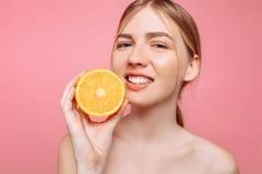 Aantrekkelijk glimlachend meisje met schone huid en oranje stukken op een roze achtergrond stock afbeelding