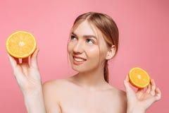 Aantrekkelijk glimlachend meisje met schone huid en oranje stukken op een roze achtergrond royalty-vrije stock foto