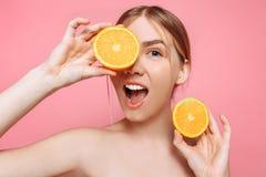 Aantrekkelijk glimlachend meisje met schone huid en oranje stukken op een roze achtergrond royalty-vrije stock foto's