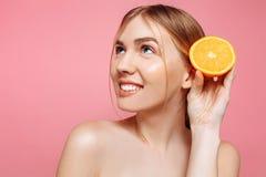 Aantrekkelijk glimlachend meisje met schone huid en oranje stukken op een roze achtergrond royalty-vrije stock afbeeldingen