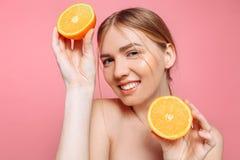 Aantrekkelijk glimlachend meisje met schone huid en oranje stukken op een roze achtergrond stock foto's