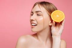 Aantrekkelijk glimlachend meisje met schone huid en oranje stukken op een roze achtergrond stock fotografie