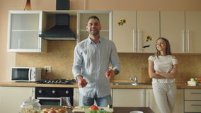 Aantrekkelijk houdend van paar die pret in de keuken hebben De knappe mens jongleert met met appelen om op zijn meisje indruk te  stock video