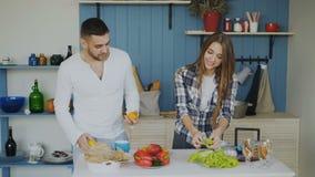 Aantrekkelijk houdend van paar die pret in de keuken hebben De knappe mens jongleert met met vruchten om op zijn meisje indruk te stock footage