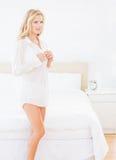 Aantrekkelijk jong blonde die omhoog wit overhemd dichtknopen Stock Afbeeldingen