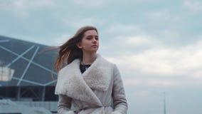 Aantrekkelijk jong Europees meisje die in de luchthaven in een warme laag benieuwd zijn Mooi meisje Winderig weer, windspelen met stock video