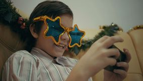 Aantrekkelijk jong jongen het spelen videospelletje of het surfen sociaal netwerk op zijn smartphone stock video